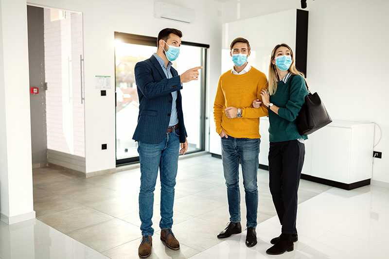 Real estate agent communicating with a couple while showing them a new apartment and wearing protective face mask due to COVID-19 pandemic.